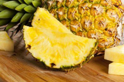 um abacaxi e fatias da fruta